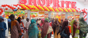 Shoppers stand outside the main entrance of the new South African retail giant Shoprite outlet in Kano, northern Nigeria, on March 20, 2014